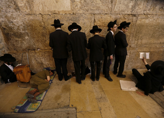 Ultra-Orthodox Jewish youths pray on Tisha B'Av at the Western Wall in Jerusalem's Old City